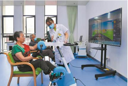 9月27日,合肥市包河区方兴社区智慧养老中心内,工作人员在指导老人进行康复训练。.png
